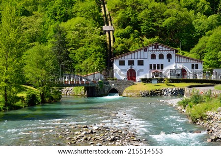Small hydroelectric power station is situated near the swift river under the forested mountain in the Pyrenees. Its building is made in the traditional Basque style.  - stock photo