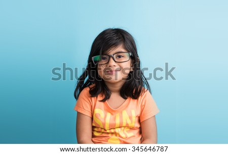 small indian girl with glasses, closeup on blue background, asian girl, 4 year indian girl, smiling, cute look, studious,black hair, long black hair, front view,passport photo - stock photo