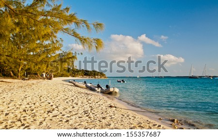 Small inflatable boats, or dinghys, along the shore of a pretty beach in the islands of the bahamas. - stock photo