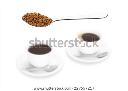 Small instant coffee chunks on a teaspoon with two coffee cups in blurred background. - stock photo