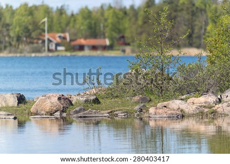 Small island at lake with trees and vegetation, red houses in background. Sweden - stock photo