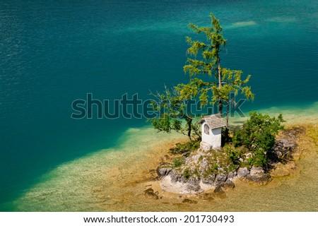 Small island in clean turquoise Wolfgangsee lake in Salzkammergut in Austria, Europe - stock photo