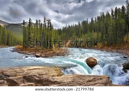 Small island in the middle of the river near to a falls - stock photo