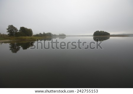 Small island on calm foggy lake water surface during early morning, Mazury, Poland - stock photo