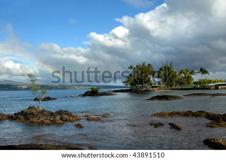 Small island on the Big Island of Hawaii is Coconut Island.  An arching metal bridge connects it to the mainland.  Recent rain storm leaves a rainbow over the Hilo area and bay. - stock photo