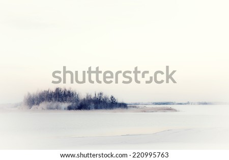 Small island out in the ice and snow a very cold winter day - stock photo