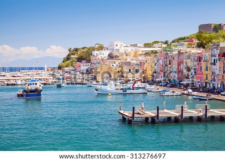 Small Italian town cityscape with colorful houses and piers. Port of Procida island, Gulf of Naples, Italy - stock photo