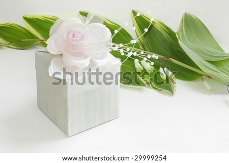 Small ivory gift box with a pink rose and some wire. - stock photo