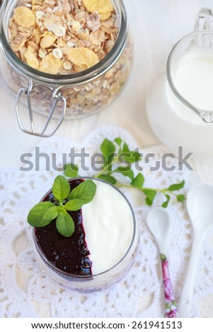 Small jar with homemade yogurt with blackcurrant jam and granola (sunflower seeds, corn, oat and barley flakes and nuts), selective focus - stock photo