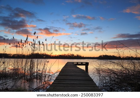 Small jetty and reed during a colorful winter sunset over a lake. - stock photo