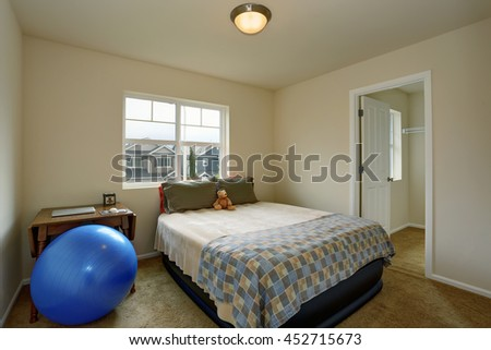 Small kids bedroom with table, blue ball and small green bed, also carpet floor and creamy walls - stock photo