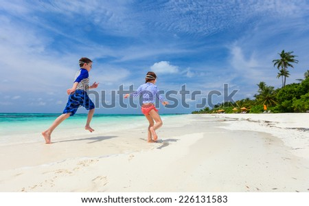 Small kids having fun at tropical beach - stock photo
