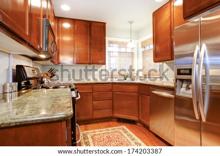 Small kitchen room with wood storage combination, modern appliances and light tone ceiling - stock photo