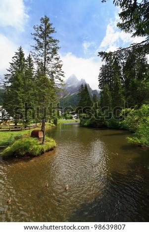 small lake with ducks in San Martino di Castrozza, Italian Dolomites - stock photo