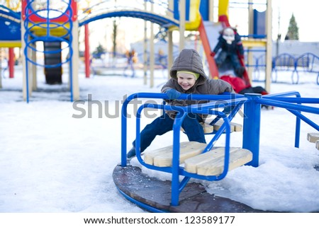 Small laughing child rides carrousel in winter - stock photo