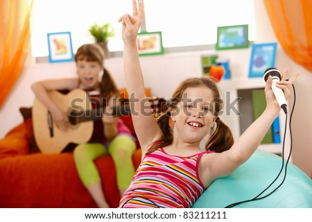 Small laughing girl with microphone, raising arms happily, friend playing guitar.? - stock photo