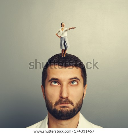 small leading woman standing on the silly man and pointing at something - stock photo