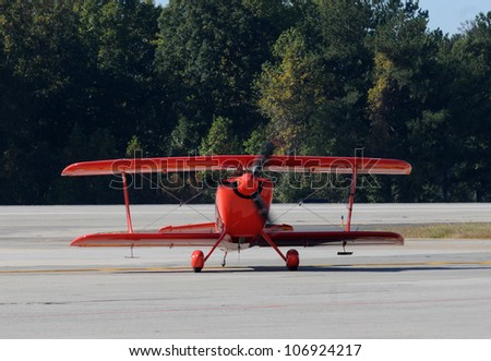 Small light aerobatic airplane painted red - stock photo