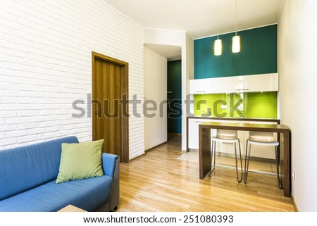 Small living room with brick wall and green kitchenette - stock photo