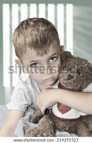 Small lonely boy with a teddy bear waiting for love - stock photo