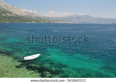 Small lonely fishing boat floating alone on adriatic sea in beach of Korcula, Croatia - stock photo