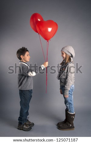 Small loving couple of kids with red heart balloons on grey background. Valentines day concept. - stock photo