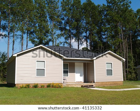 Small low income home with tan vinyl siding. - stock photo