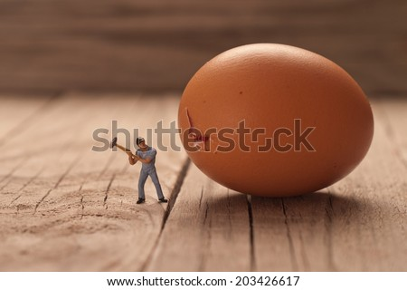 Small man breaks an egg. The concept of cooking.  - stock photo