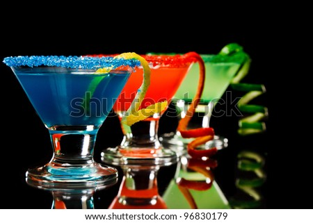 small martini glasses poured and garnished with sugar rims all different colors - stock photo