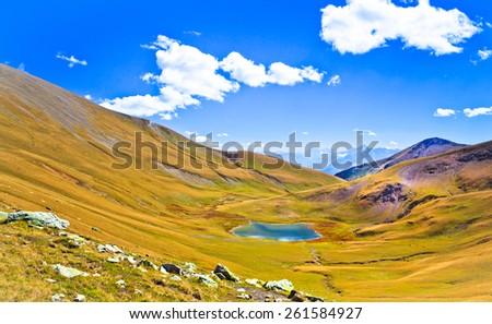 Small mountain lake under blue sky with clouds.Picture was taken during trekking hike in beautiful and stunning Caucasus mountains, autumn, Arhiz region,Abishira-Ahuba range,Karachay-Cherkessia,Russia - stock photo