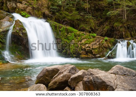 Small mountain waterfall on the rocks covered with moss in the forest - stock photo