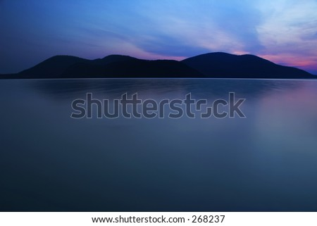 Small mountains and water reflection - stock photo