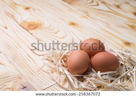 Small nest with eggs on wooden desk - stock photo
