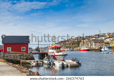 Small Norwegian village landscape, wooden houses and moored fishing boats on the North sea coast  - stock photo