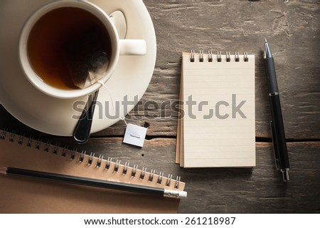 Small notepad with a cup of tea, pen and pencil on rustic wood background with low key scene - stock photo