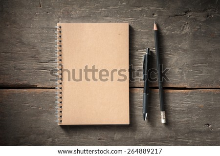 Small notepad with pen and pencil on rustic wood background with low key scene. - stock photo