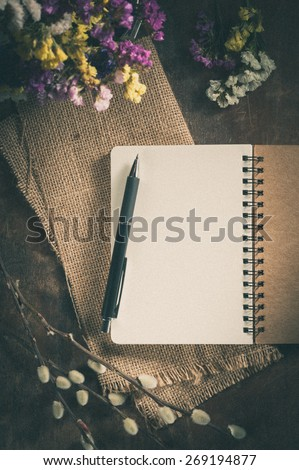 Small notepad with pen on rustic wood background with film filter effect - stock photo
