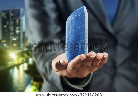 Small office building standing on the human palm - stock photo