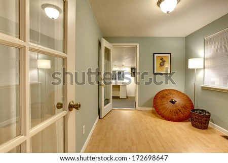 Small office room with hardwood floor and olive walls - stock photo