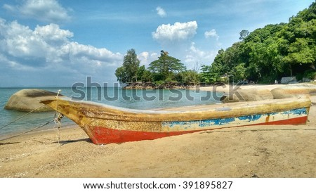 Small old unused boat in some kind of vintage style laying on a beach at a tropical island. Palms, other trees and the blue bright sky are forming the background. - stock photo