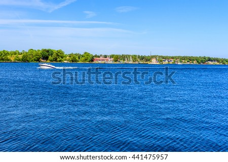 Small open motorboat traveling in the Swedish archipelago of Vastervik on a fine summer day. - stock photo