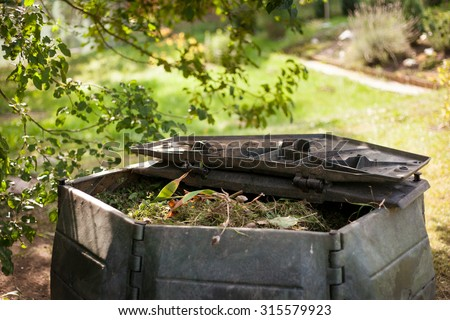 Small outdoor composting bin for recycling kitchen and garden organic waste - stock photo