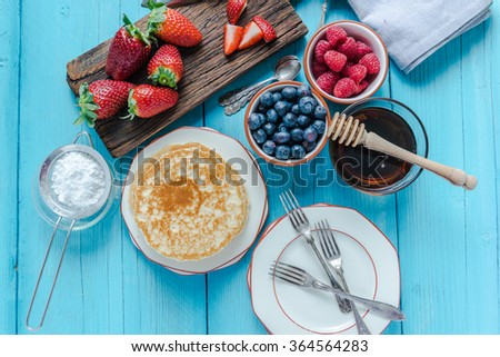 Small pancakes stack and fruits and honey - stock photo