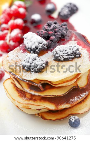 Small pancakes topped with syrup, currants and blackberry on white background - stock photo