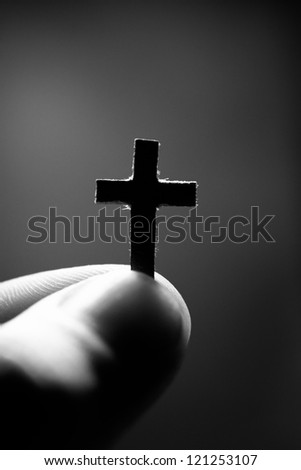 Small paper cross in finger. Faith concept. - stock photo
