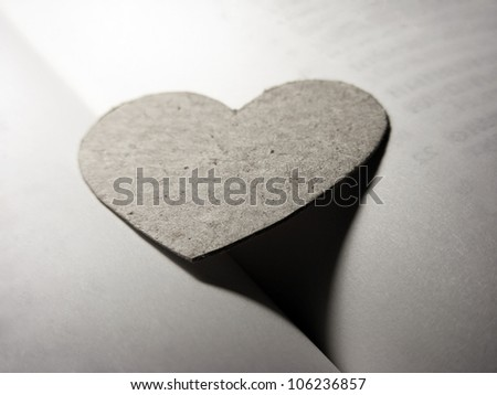 Small paper heart on a book. Black and white style. Selective focus. - stock photo
