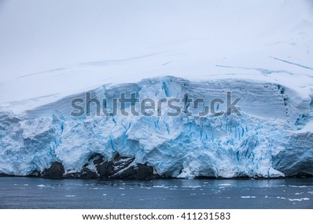 Small part of the blue larger iceberg in ocean, Antarctica  - stock photo