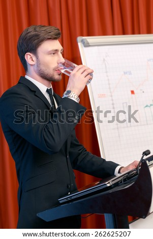 Small pause in presentation. Good-looking business manager in classical black suit drinking a glass of water while standing at the tribune with flipchart on the background - stock photo