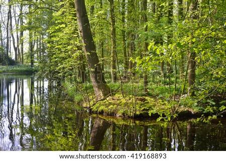 Small peaceful canal surrounded by green spring bushes in Netherlands - stock photo