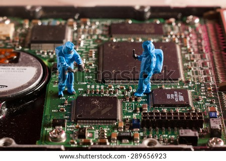 Small people control the electronic parts. The concept of technological research. - stock photo